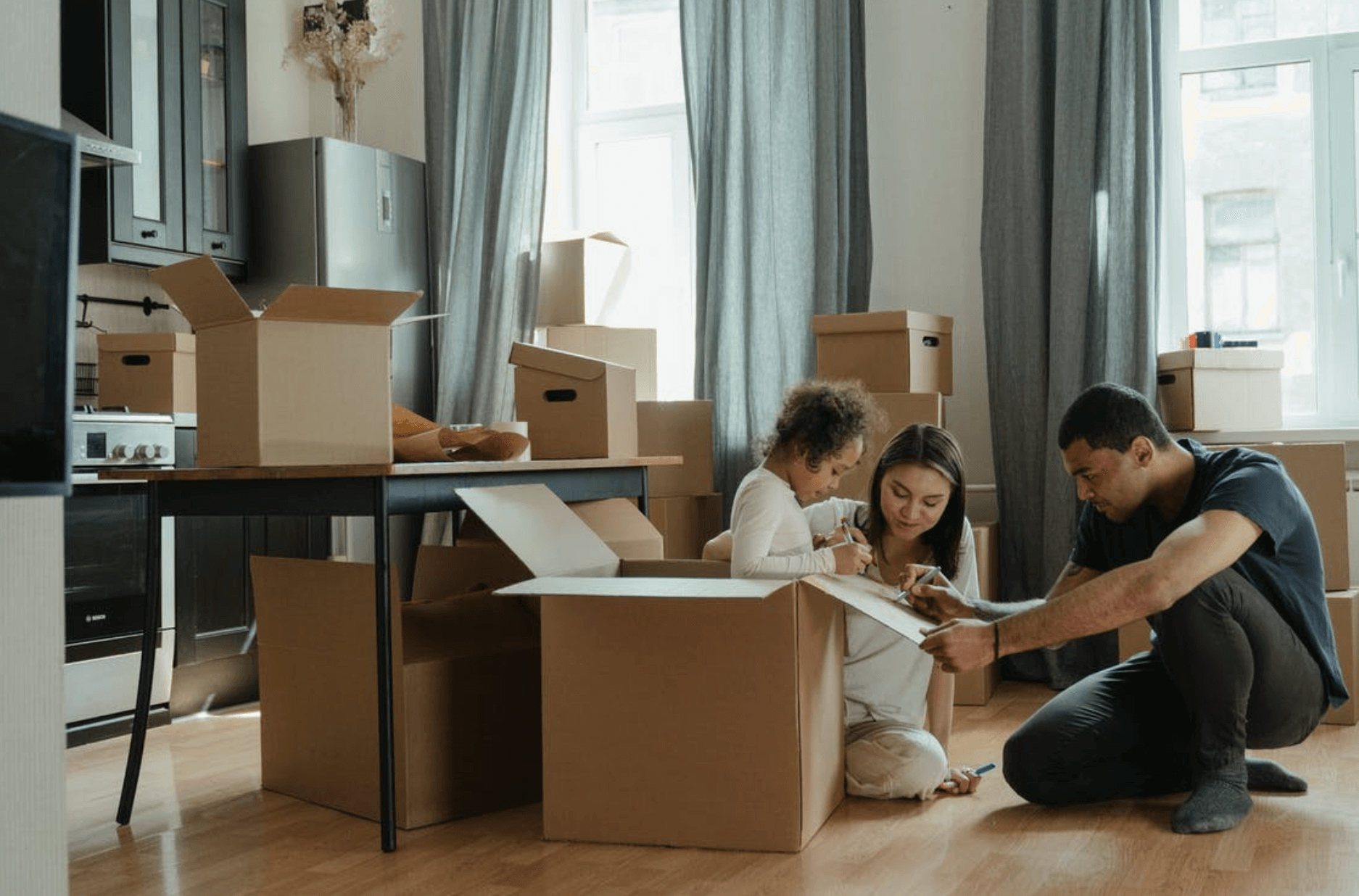 A family of three surrounded by packing boxes
