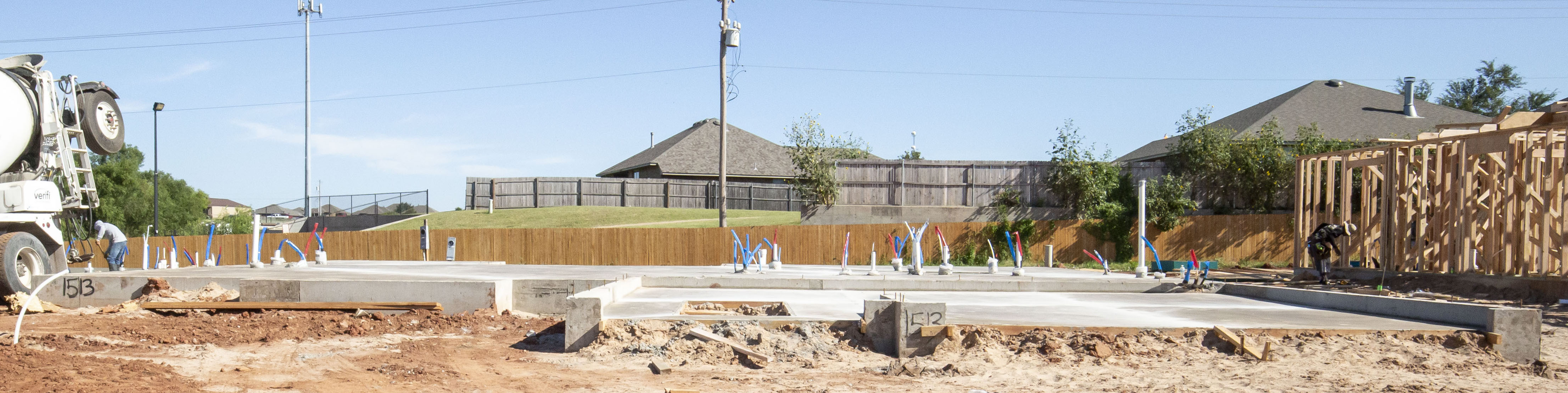 A foundation on a plot of land with a concrete truck on the left and the frame of a home on the right.
