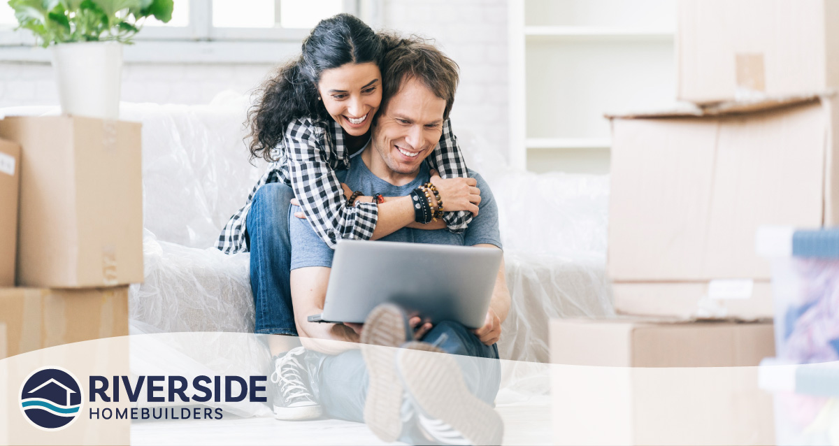 Image of a woman hugging her partner while he looks at a laptop.