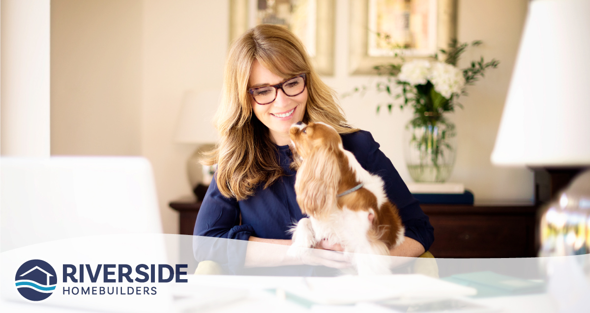 Woman sitting at desk at home with her dog on her lap.