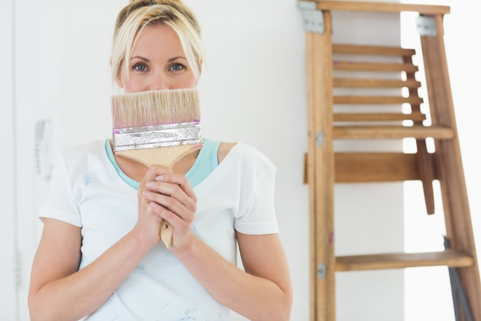 A woman holding a paintbrush, representing the yearly home maintenance checklist of custom home builder Robertson Homes in Michigan