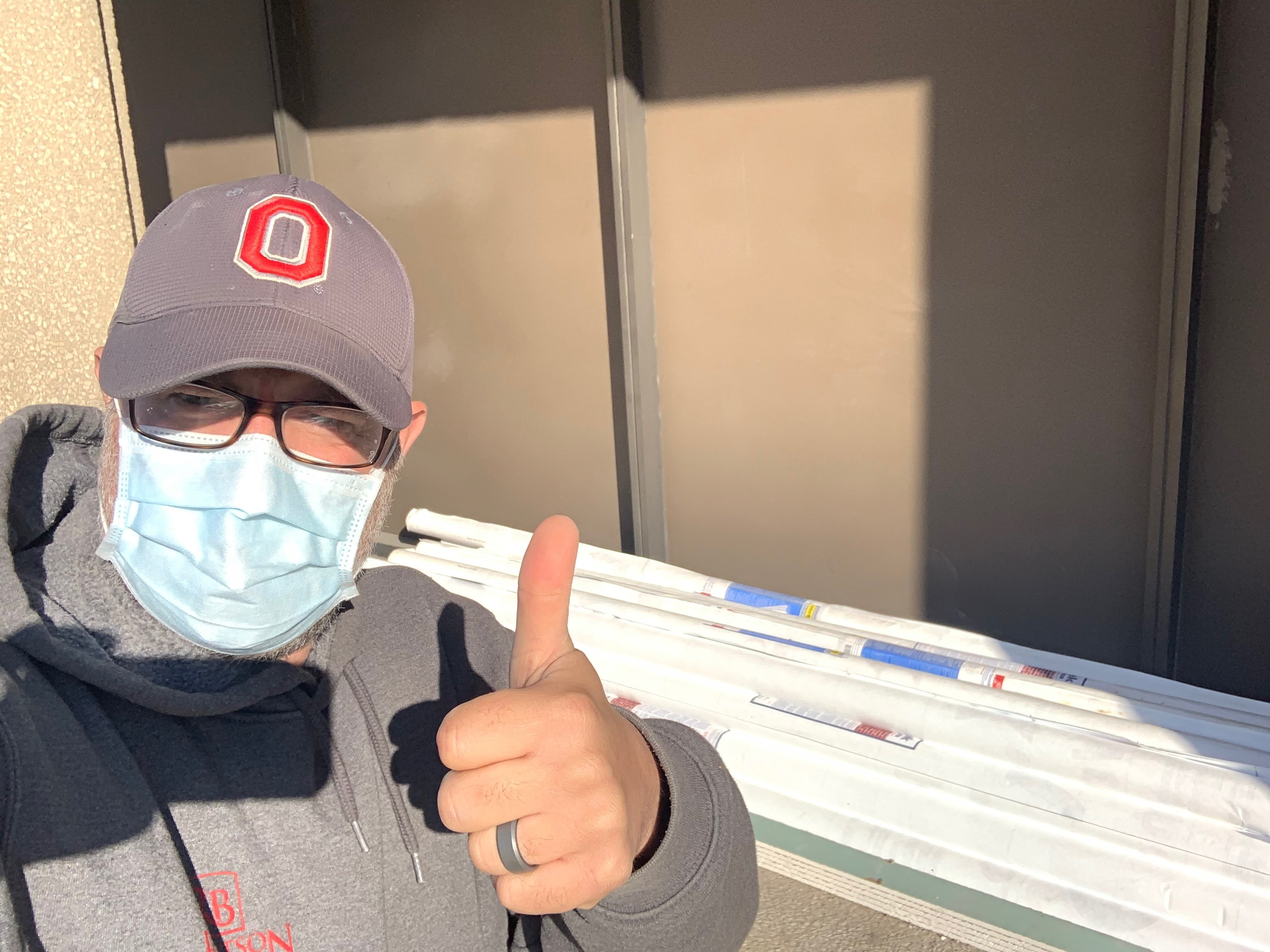 Man wearing mask giving thumbs up in front of donation