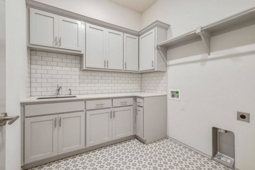 Utility room gray cabinets subway tile decorative tile