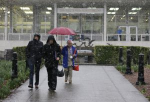 Pedestrians walk in front of the Washington State Library during a brief snow shower Feb. 23 at the Capitol in Olympia. (AP Photo/Ted S. Warren)
