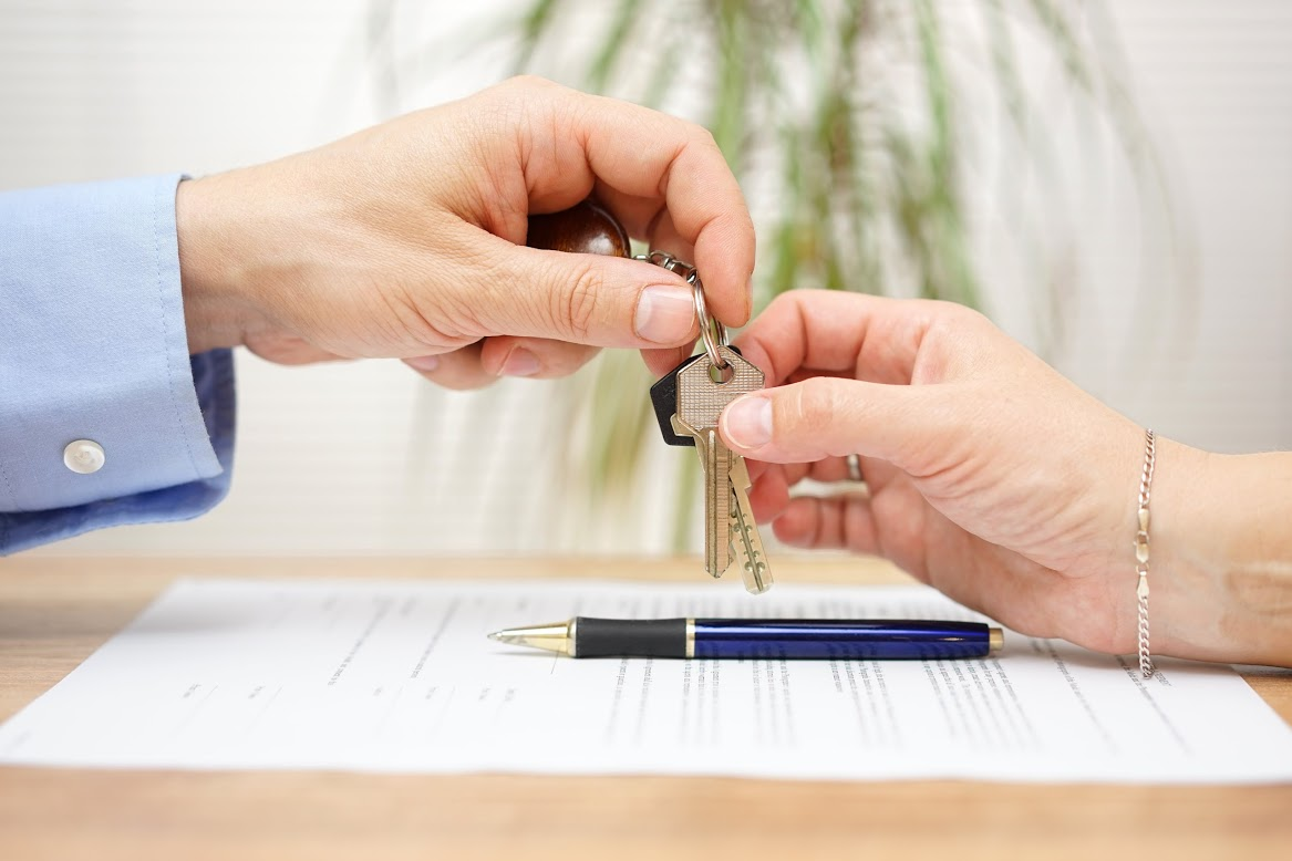 One person handing keys to another person over a document and a pen