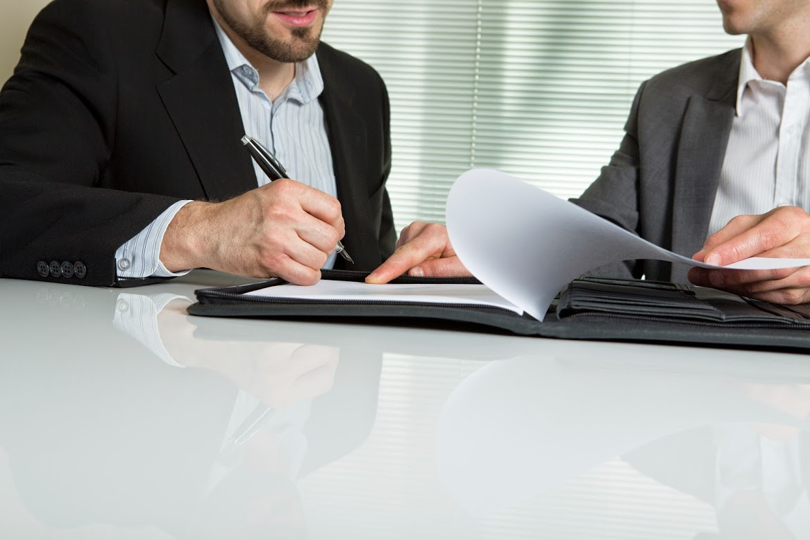A man signing papers representing  a homeowner signing contracts with a real estate agent
