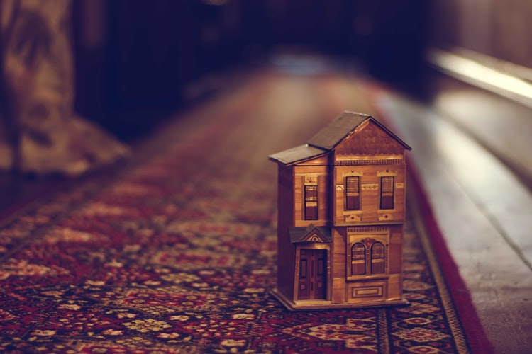 Toy two story house sitting on a rug in a hallway