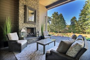 Outdoor Living Area with Stone Fireplace Surround, Seating, Water Feature, Cooking, and Dining 1of 2