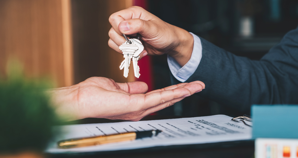 Man in suit handing new homeowner the keys to a house
