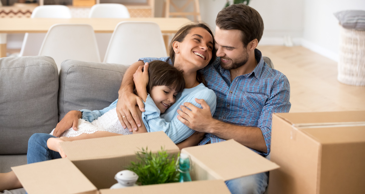 Two parents and child laying on couch next to a moving box.