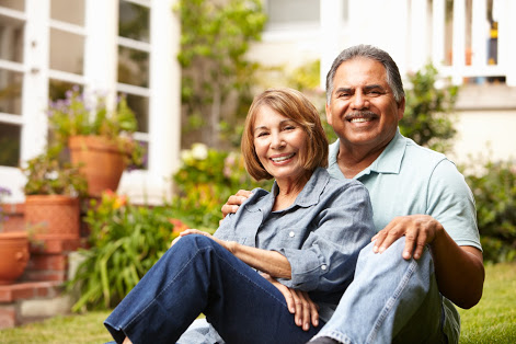 An older couple smiling in their backyard