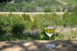 Glass of white wine overlooking the scenic Texas hill country near Belle Oaks