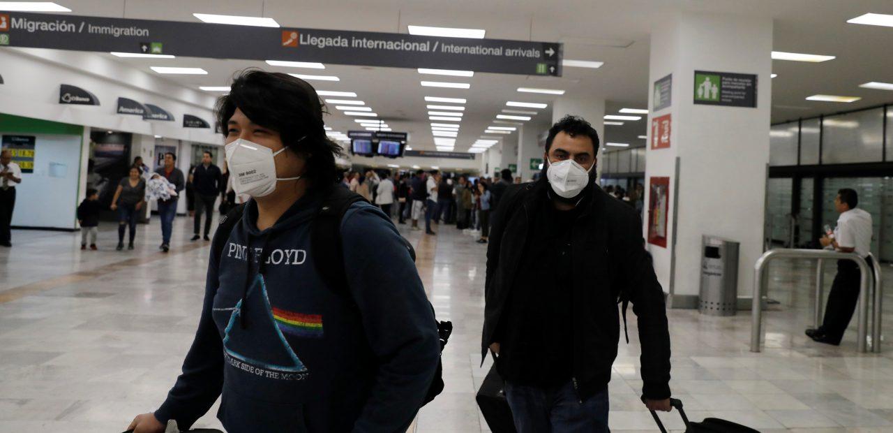 Pasajeros de China Southern Airlines utilizan cubre bocas al llegar al aeropuerto de la Ciudad de México