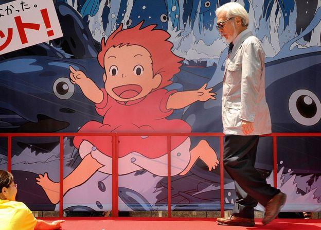 """Hayao Miyazaki camina frente a un arte de """"Ponyo""""."""