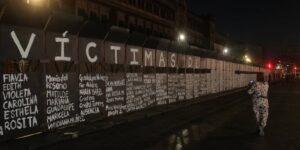 Mujeres escriben los nombres de víctimas de feminicidio en vallas de Palacio Nacional