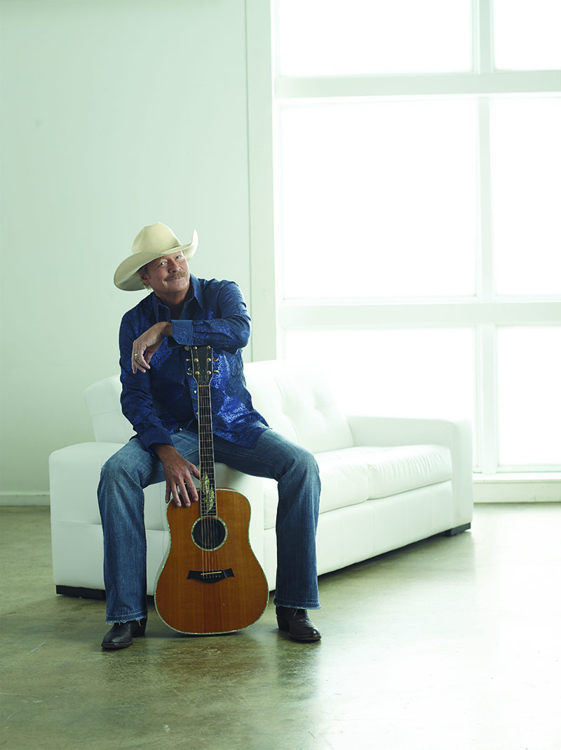 Image of Alan Jackson sitting in a sunfilled room on a white, leather couch and leaning against his guitar smiling to the camera