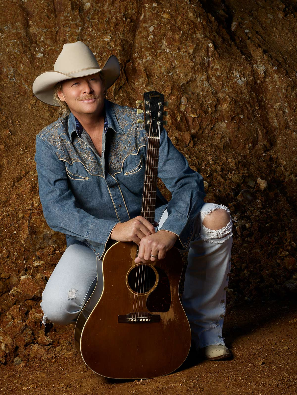 Image of Alan Jackson crouched down on one knee embracing his acoustic, brown guitar and wearing a blue cowboy shirt and tan colored hat