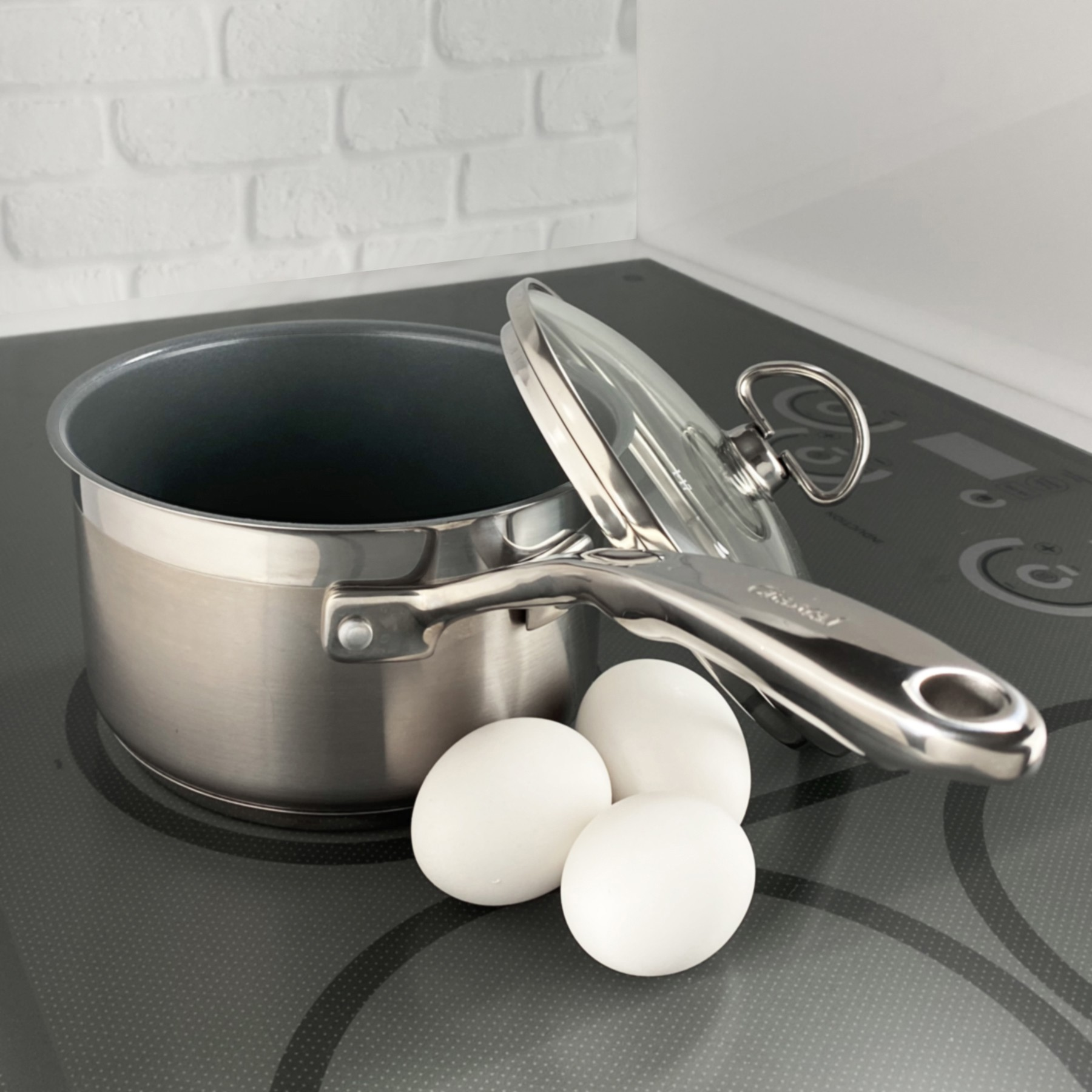 Stainless Steel saucepan chantal induction 21 steel collection premium no nickel non-toxic cookware 2 quart capacity with glass lid brushed exterior image showing pan on cooktop with eggs