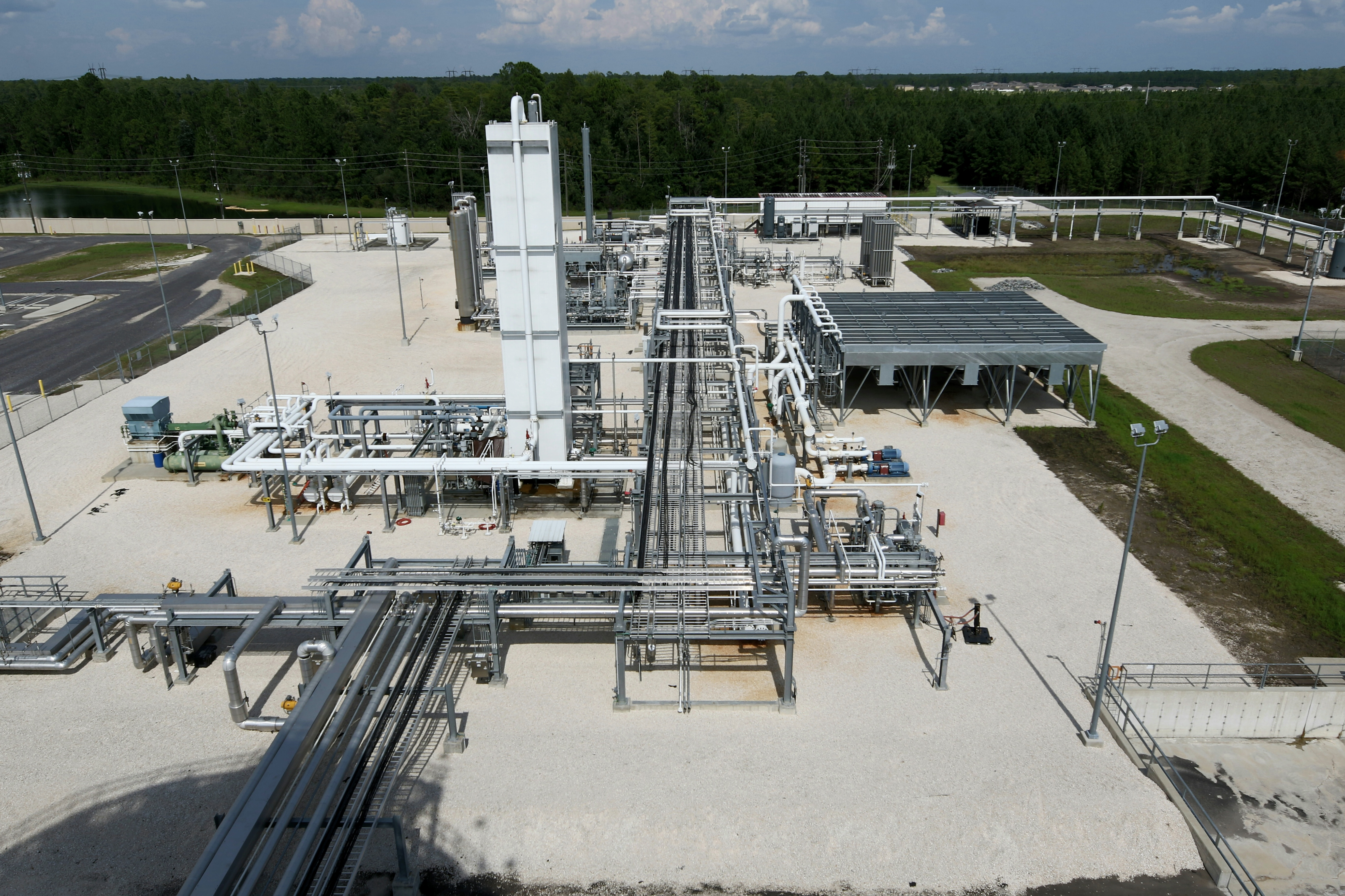 aerial image of a natural gas plant featuring a maze of intertwining chrome and white piping surrounding a tall white tower