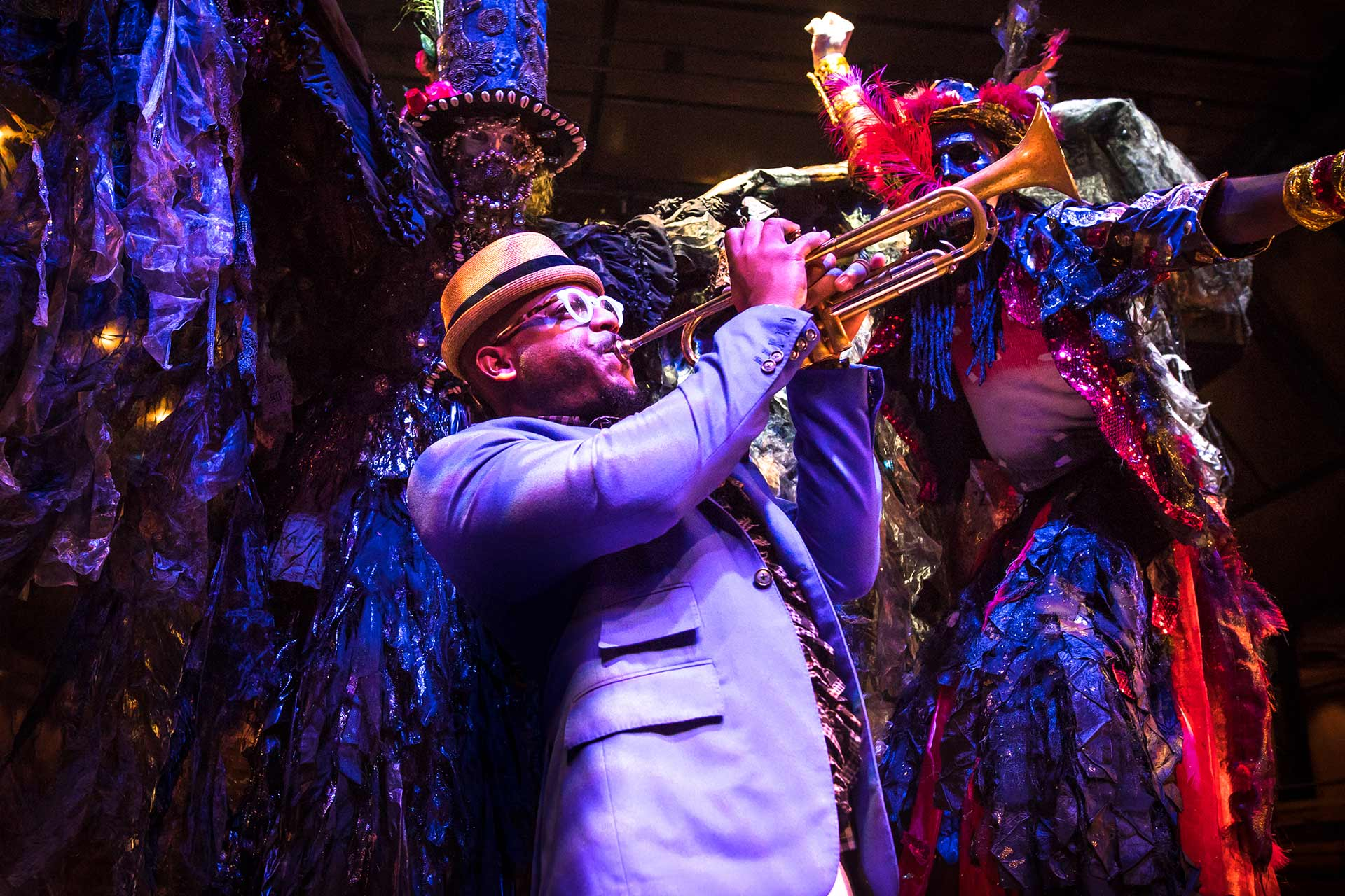 Etienne Charles playing trumpet against a colorful, mardi gras inspired color treatment and performing artists wearing masks and costumes on stilts.