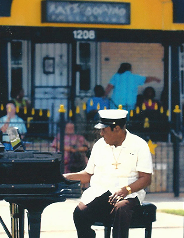 Fats in front of his house at the piano after Hurricane Katrina