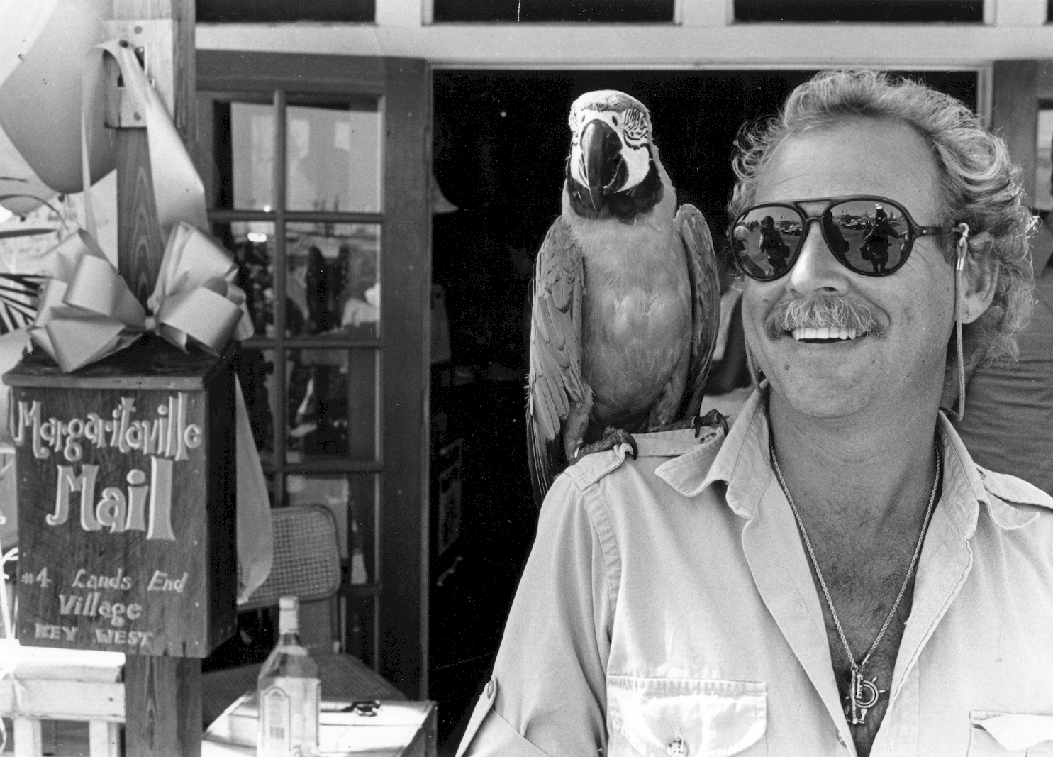 Black and White image of Jimmy Buffet standing outside a Key West novelty shop, smiling with open shirt and wearing large avaitor sunglass with a large parrot perched upon his right shoulder.