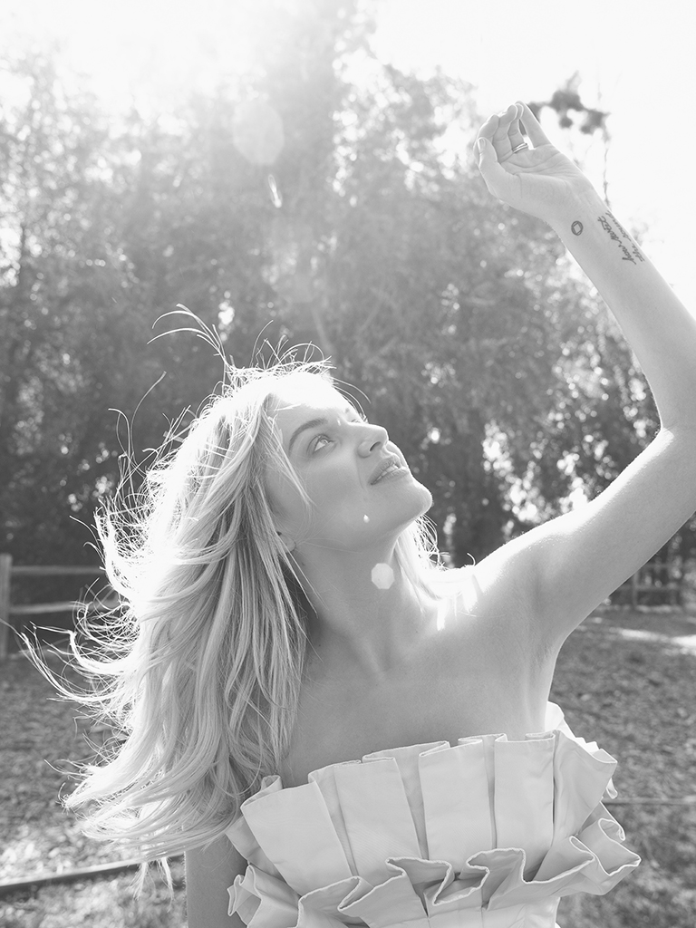 black and white photo Kelsea Ballerini reaching towards the sky