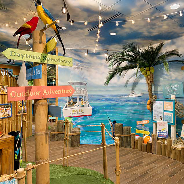 picture of an island-inspired bamboo walkway, rustic wooden signs pointing to daytona and hilton head with hanging string lights and ocean imagery