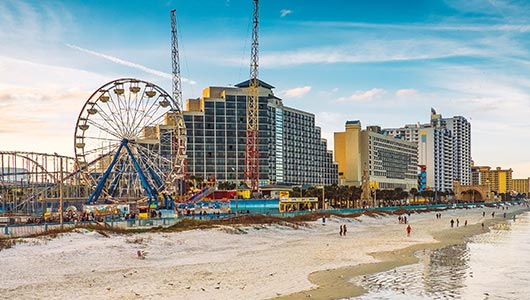 Photo of Daytona Beach, Florida ferris wheel and sandy beach. Visit our Latitude Margaritaville Daytona Beach location, hotels, properties, amenities and homes under 200 thousand dollars