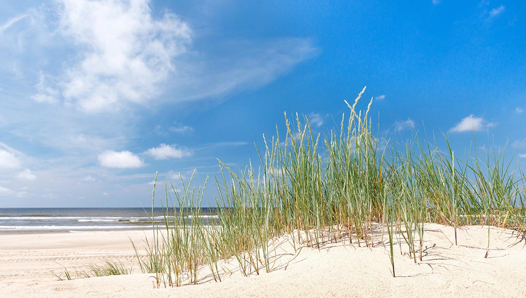 Photo of Hilton Head, South Carolina, Lighthouse, sandy beach and surf. Visit our Latitude Margaritaville Daytona Beach location, hotels, properties, amenities and homes under 200 thousand dollars