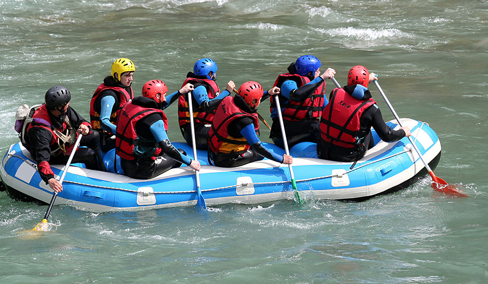 group of people whitewater rafting in a moving river wearing helmets and holding paddles