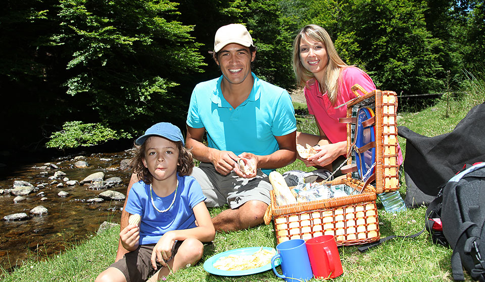 a young family enjoying a picnic near a stream wearing colorful clothes and smiling