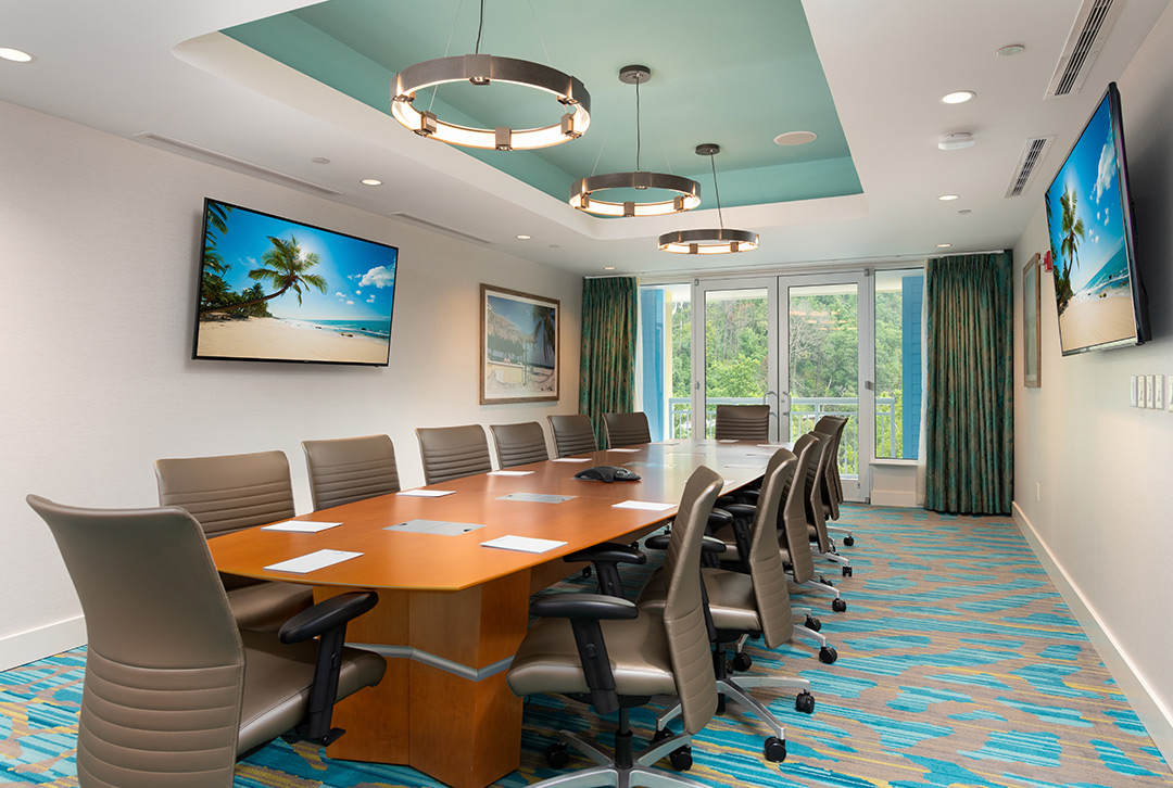 Image of a lavishly appointed board room with turqoise accented blue carpeting and large, high-back tan colored chairs surrounding a teak wood board room table