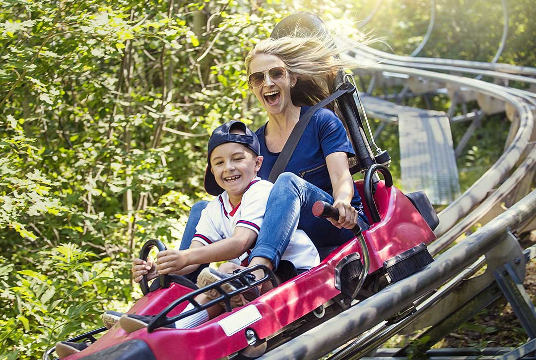 A woman her son zooming down the tracks of a speeding roller coaster