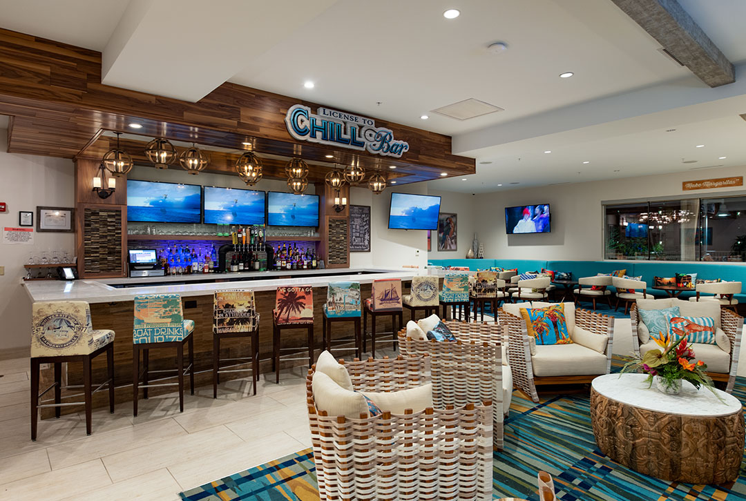 Image of the License to Chill bar front, multi-printed barstools overlooking wide screen tvs behind the bar and a  comfortable, central seating area just feet from the serving counter.