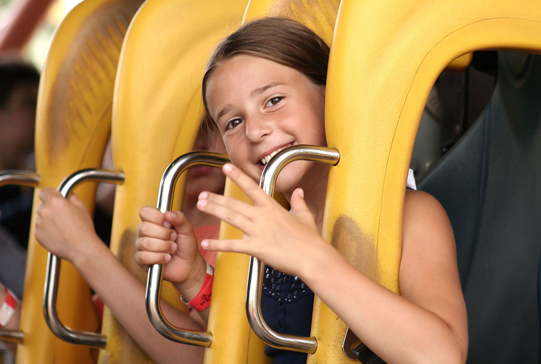 A young girl sits in the padding of a fair ride