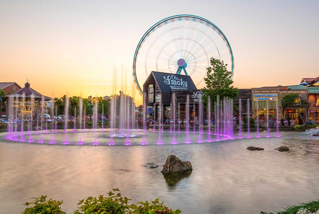 Image of the Gatlinburg Resort complex in front of a large, colorful fountain at sunset