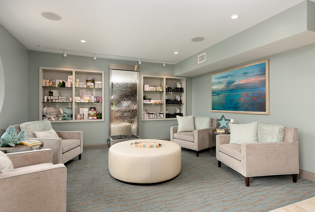 Image of the spa waiting room with several light tan large, upholstered chairs and couch, spa accessories for sale and brightly colored seafoam colored walls