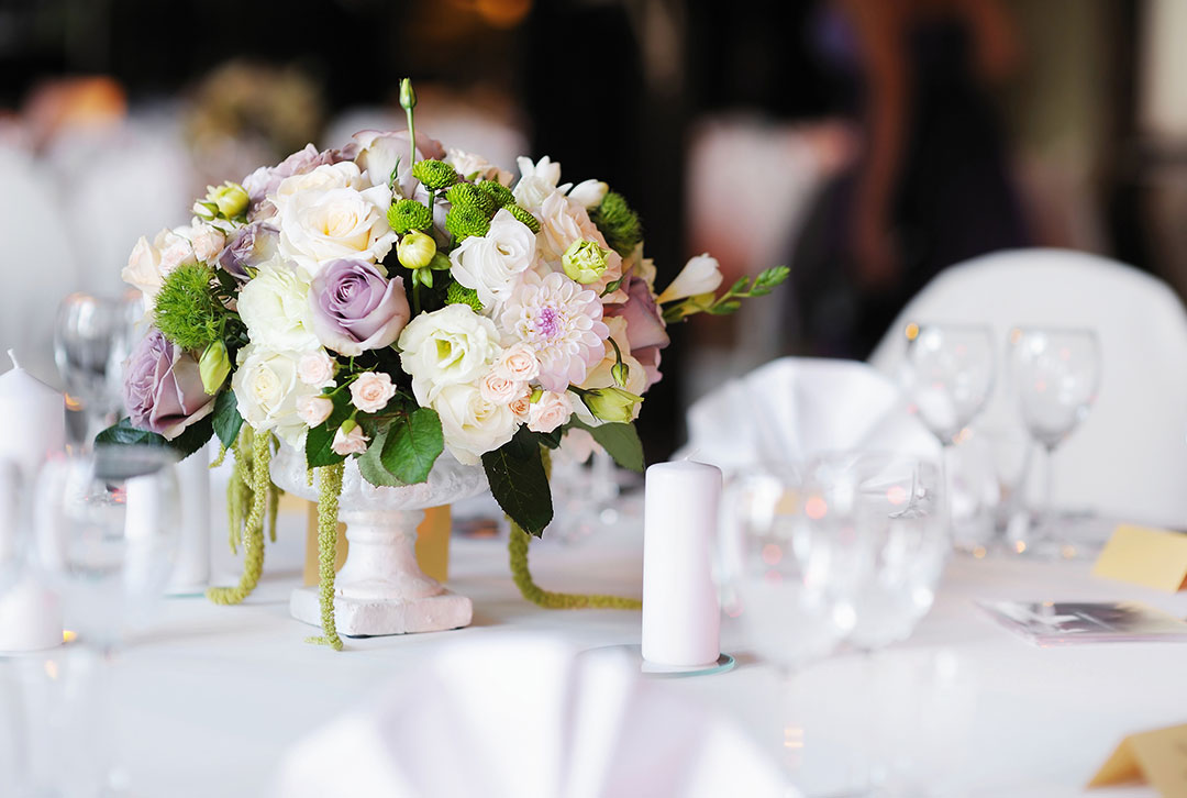 White clothed wedding tables with white adornments of flowers and placesettings