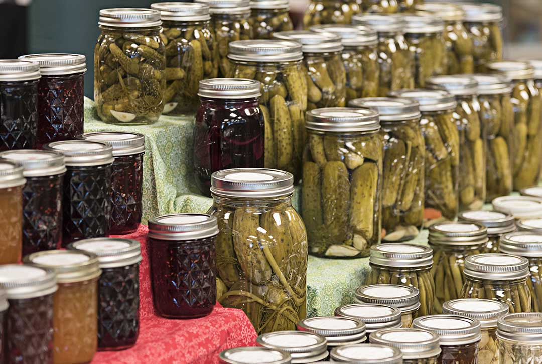 Jars of canned vegetables, pickles and spices