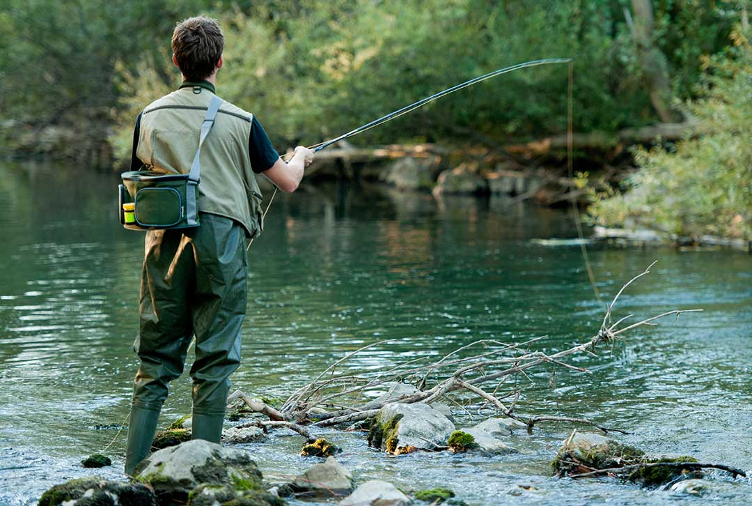 Man stading on rocks fishing in a river with a fly rod