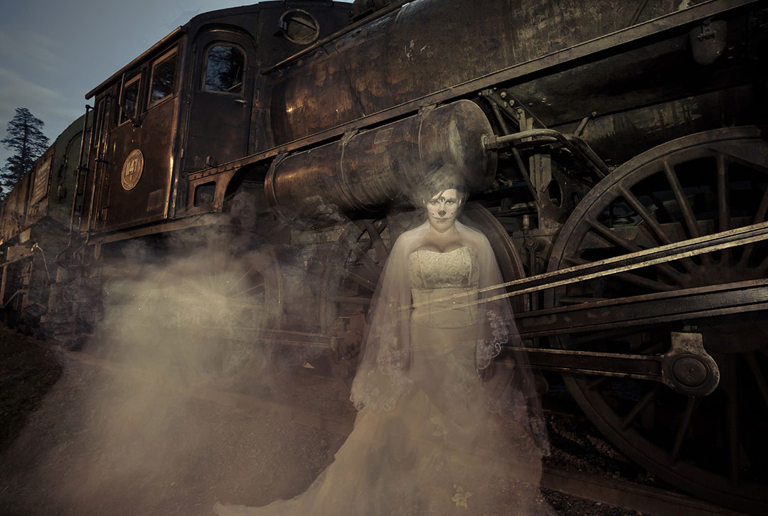 Ghostly picture of a turn of the century woman dressed in victorian to the side of a rusty locomotive