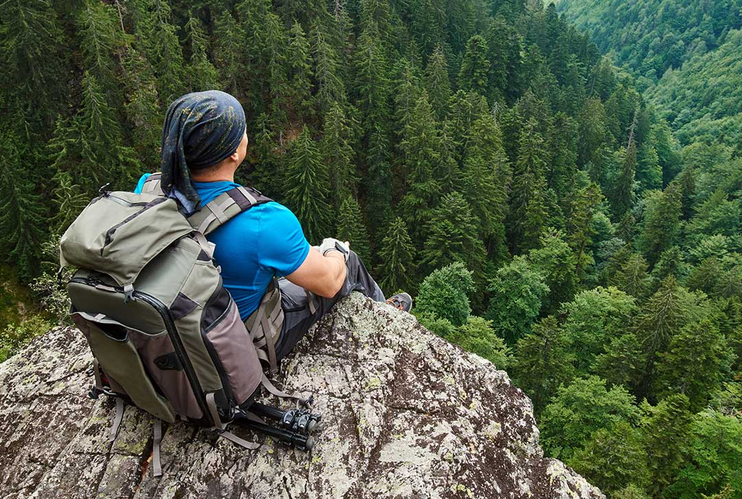 Man taking a break from hiking, sitting a rock overlooking the tree lined forest below