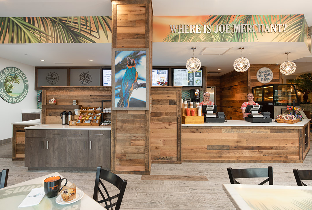 Image of Joe Merchant's coffee bar and cafe area featuring refreshments, self-serviing accessories under a palm printed banner and island-inspired color scheme