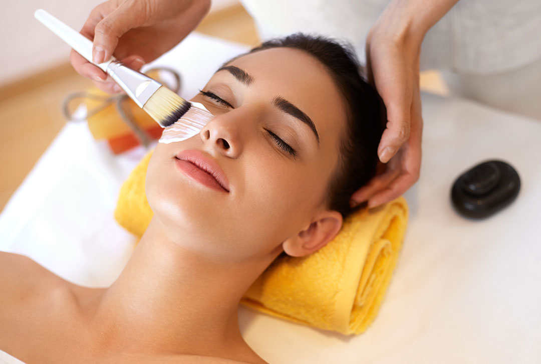 A woman relaxing on a massage table getting pampered with a facial cleansing