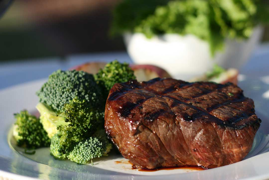 Image of a New York steak, broccoli and side salad