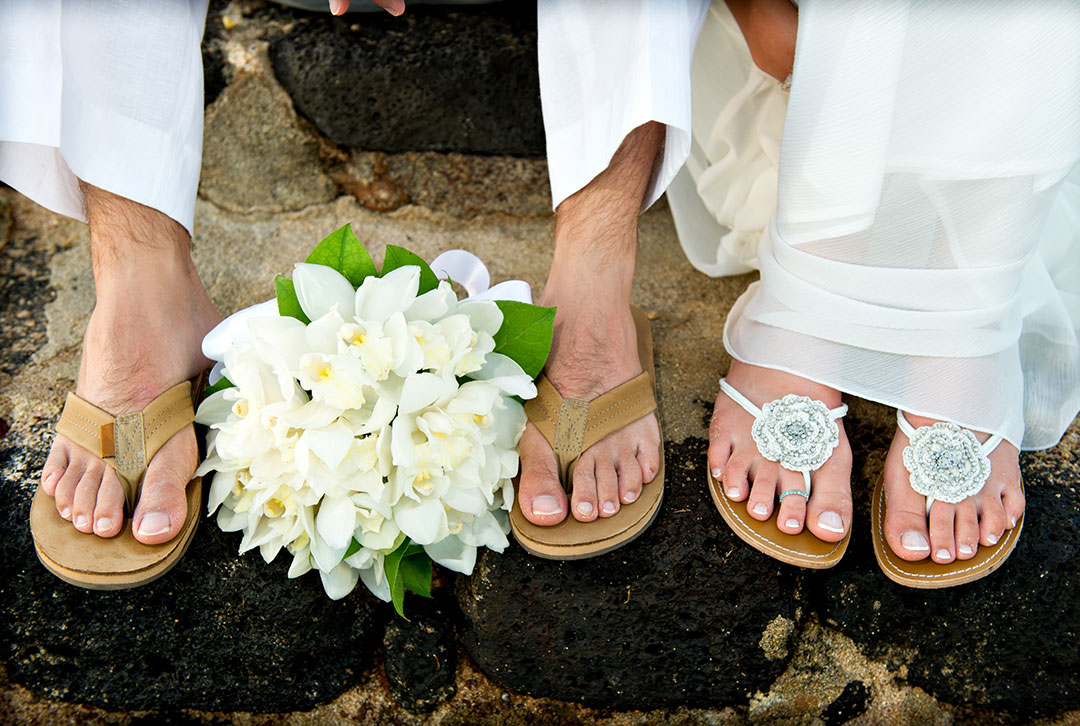 A man and woman sitting down, wearin flip flops with a wedding bouqut between the feet of the man