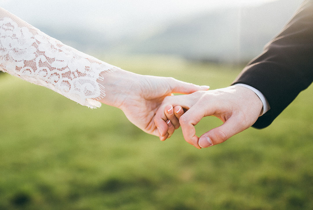 Image of a man and woman holding hands, she wearing a wedding dress of lace and he is wearing a tuxcedo