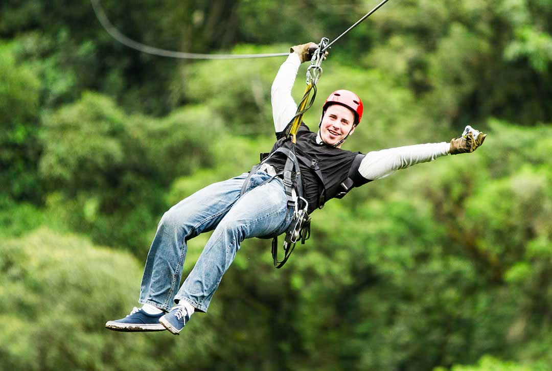 Man enjoying a zip line, waving his arms over his head, wearing a helmet