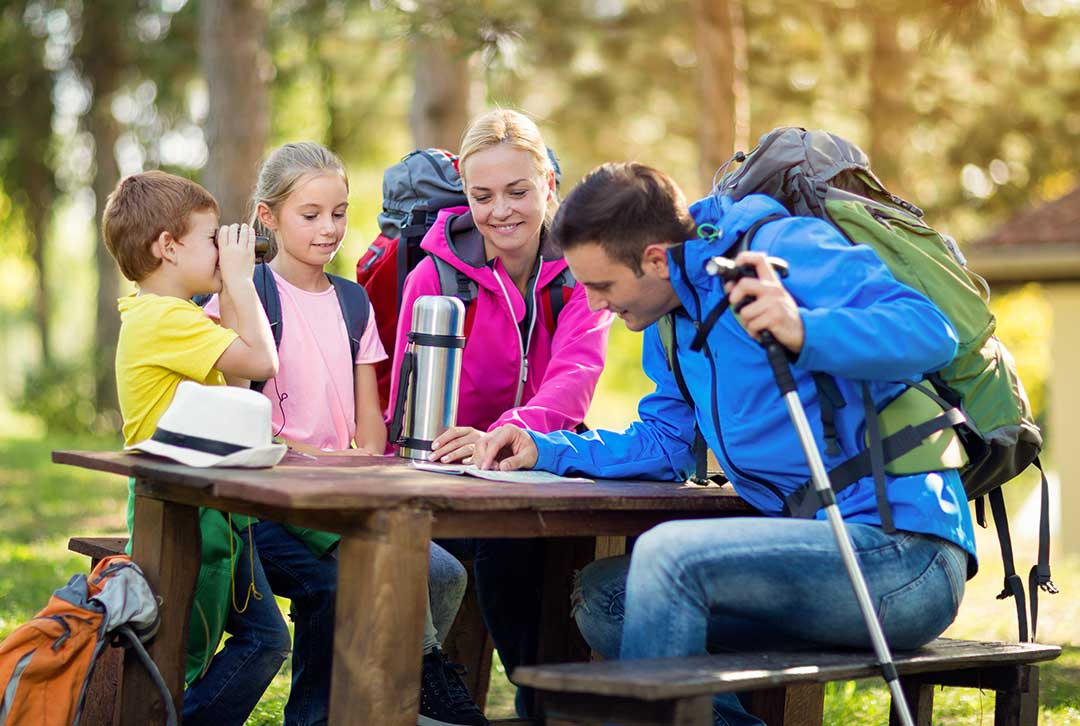 Family enjoys a side road picnic table while review a travel map